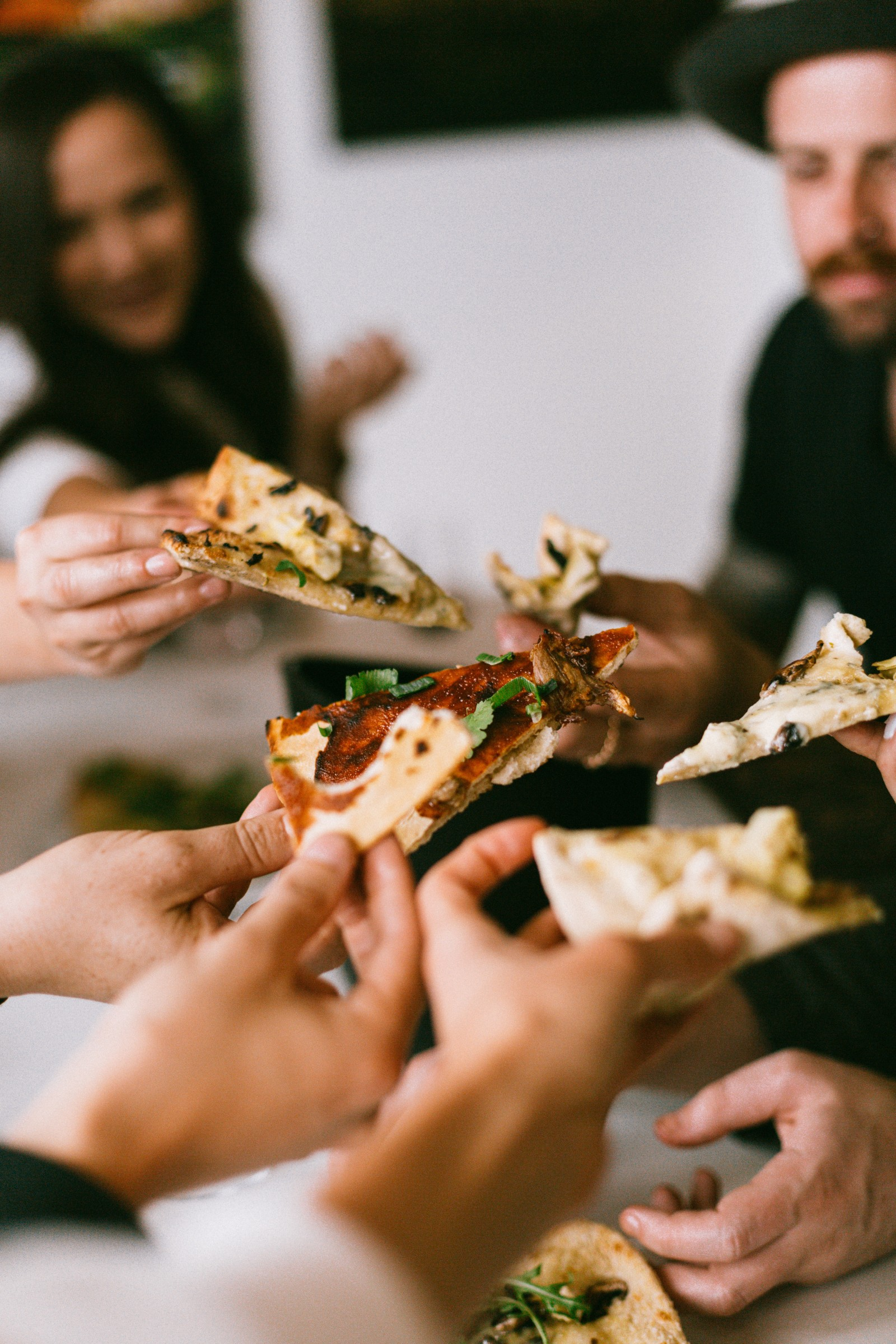 People sharing slices of pizza